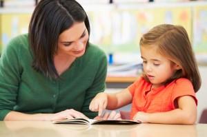 stockfresh 4360683 elementary-pupil-reading-with-teacher-in-classroom sizeS edb970